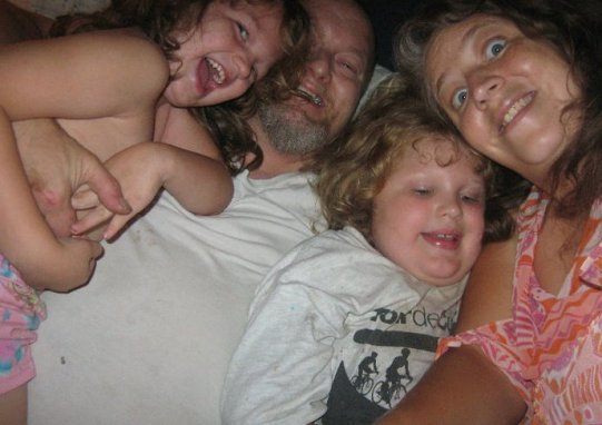 The family that laughs together -  some time ago, on our couch, in a pile.