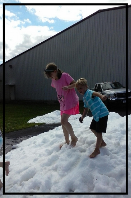 """August """"snow""""; no shovel needed! Lise and friend Logan playing in the Zamboni shavings at Clifton Commons Playground/skating rink."""